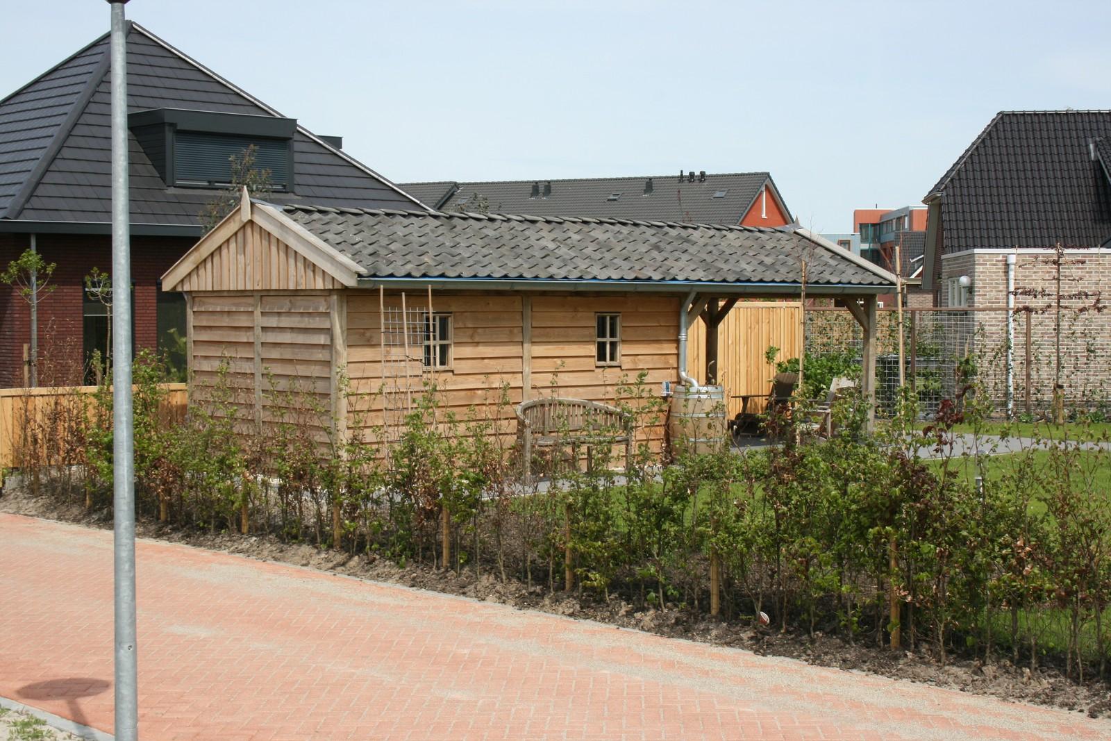 Robuuste_tuinhuis - Houten garage met grote carport op maat gemaakt.