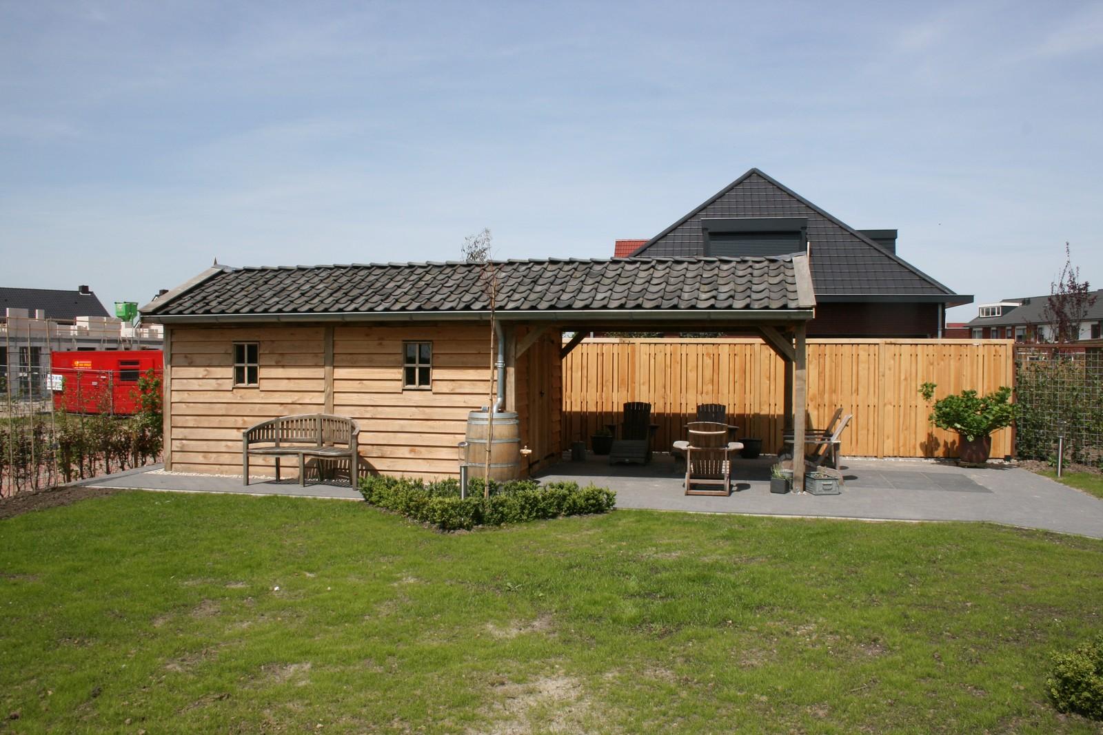 tuinhuizen - Houten garage met grote carport op maat gemaakt.
